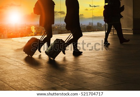 people and traveling luggage walking in airport terminal building with sun set sky at urban scene and air plane flying background Royalty-Free Stock Photo #521704717