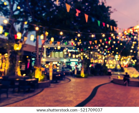 abstract blur image of food stall at night market festival for background usage . (vintage tone) Royalty-Free Stock Photo #521709037