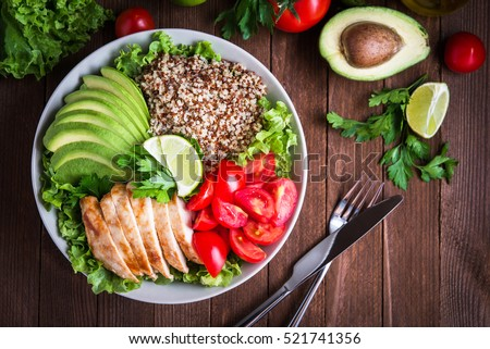 Healthy salad bowl with quinoa, tomatoes, chicken, avocado, lime and mixed greens, lettuce, parsley on wooden background top view. Food and health. #521741356