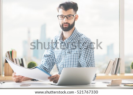Handsome young businessman doing paperwork at workplace #521767330