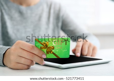Woman with gift card and tablet, closeup. Shopping online. Holiday celebration concept. #521773411