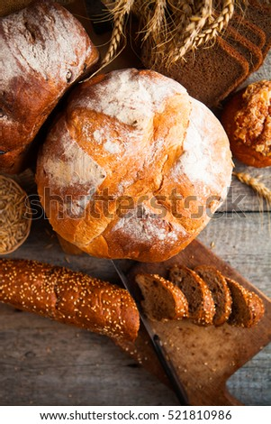 Fresh bread and wheat on the wooden table background #521810986