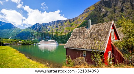 Red cottage against cruise ship in fjord, Flam, Norway