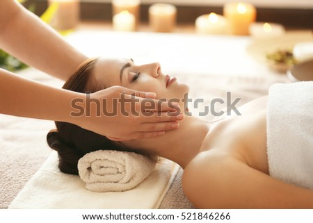 Spa concept. Young woman enjoying of facial massage in spa salon #521846266