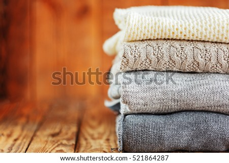 Pile of knitted winter clothes on wooden background, sweaters, space for text #521864287