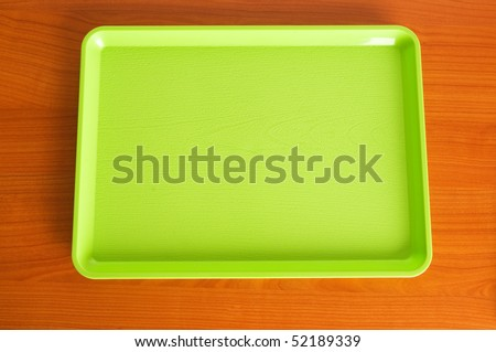 Green tray on the wooden table #52189339