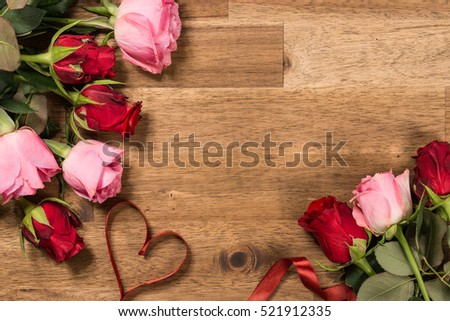 Roses  and red ribbon on wooden background. Valentines day background #521912335