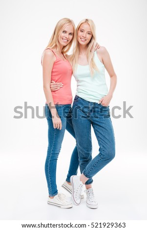 Picture of happy girls dressed in jeans ant t-shirts posing. Isolated over white background. Looking at the camera.