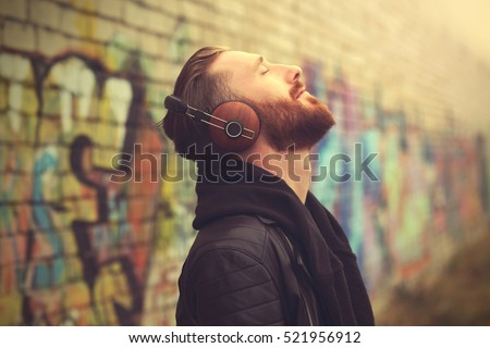 Handsome man in headphones listening to music outdoors Royalty-Free Stock Photo #521956912
