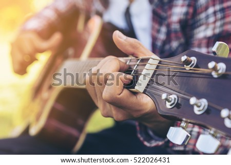 Man 's hand playing acoustic guitar, folk song. Nature background. #522026431