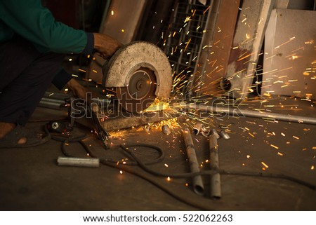 Worker use Electric grinder cutting metal with sparks in workshop #522062263