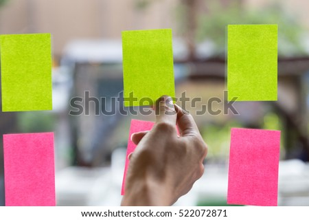 young businesswoman with colleague sticking adhesive notes on window in office #522072871