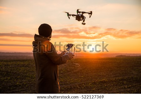 Man operating a drone with remote control. Dark silhouette against colorful sunset. Soft focus. #522127369