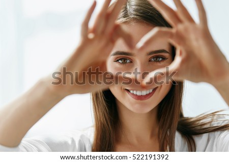 Healthy Eyes And Vision. Portrait Of Beautiful Happy Woman Holding Heart Shaped Hands Near Eyes. Closeup Of Smiling Girl With Healthy Skin Showing Love Sign. Eyecare. High Resolution Image Royalty-Free Stock Photo #522191392