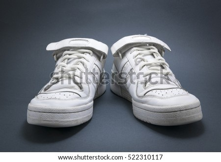 White basketball sneakers on blue background with black vignette. #522310117