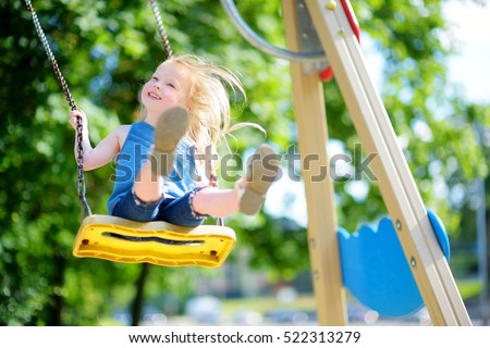Cute little girl having fun on a playground outdoors in summer Royalty-Free Stock Photo #522313279