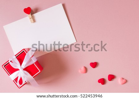 Valentine day composition: red gift box with bow, stationery / photo template with clamp and small hearts on light pink background. Top view. #522453946