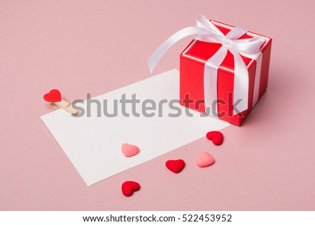Valentine day composition: red gift box with bow, stationery / photo template with clamp and small hearts on light pink background. #522453952