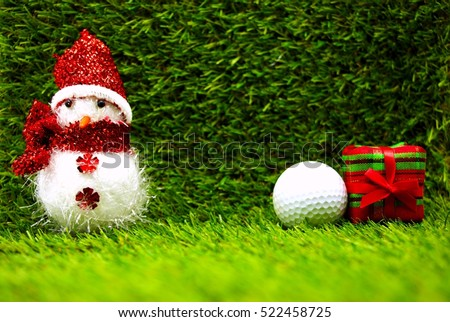 Snowman with golf ball and Christmas gift box on green grass background