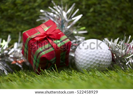 golf ball and Christmas gift box on green grass background