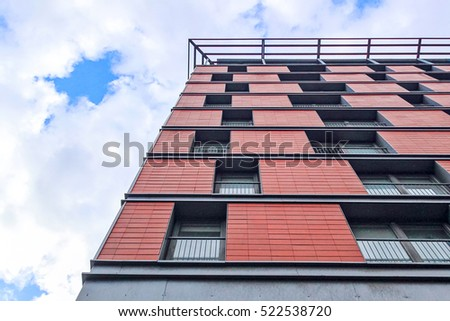 Red window building pattern. Grid pattern on a building in Glasgow. Red and grey colors. Detail photo of exterior urban architecture taken during sunny day. #522538720