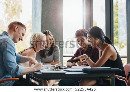 Happy young university students studying with books in library. Group of multiracial people in college library. Royalty-Free Stock Photo #522554425