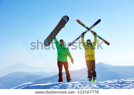 Skier and snowboarder stands mountain top with ski and snowboard in hands. Skiing and snowboarding concept. Sheregesh ski resort #522567778