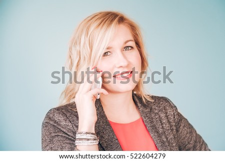 Pretty happy smiling woman in red blouse and business costume jacket communicating over white smartphone against pale teal blue background #522604279