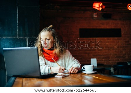 Young freelancer woman using laptop computer sitting at cafe table. Happy Smiling Girl Working Online Or Studying And Learning While Using Notebook. #522644563