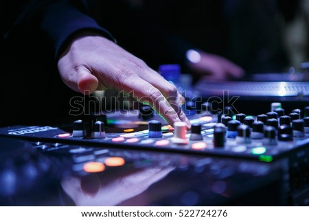 MOSCOW - 15 NOVEMBER,2016: DJ play music show on stage in night club.Disc jockey mix tracks on sound mixing controller,pro audio equipment.Focus on hands #522724276