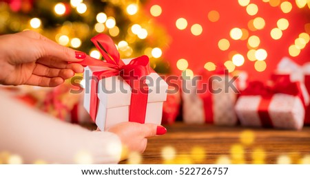 Detail of woman hands opening Christmas gift with blur abstract background #522726757