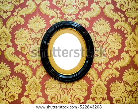 Oval wall picture frame at center on classic wallpaper with copy space