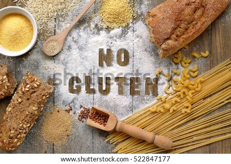Gluten free flour and cereals millet, quinoa, corn flour polenta, brown buckwheat, basmati rice, bread and pasta with text no gluten in English language with spoon on brown wooden background,up view Royalty-Free Stock Photo #522847177