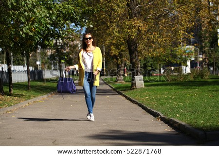 Beautiful woman in yellow coat walking autumn street #522871768