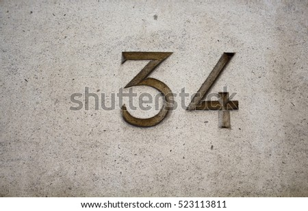 View of engraved building number (34) in Paris on stone surface/wall.