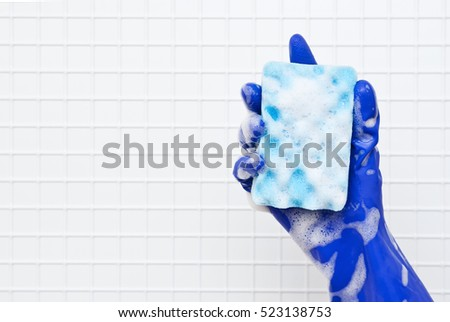 Hand in blue glove small blue sponge in the foam on a background of white tiles #523138753