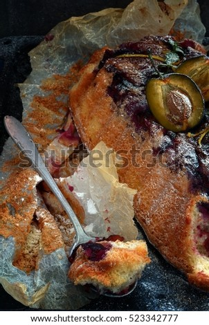air sponge cake with plums and icing sugar on a dark background #523342777