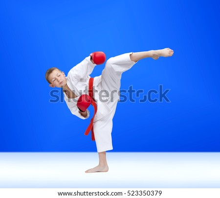 Karateka hits a kick on a blue background #523350379