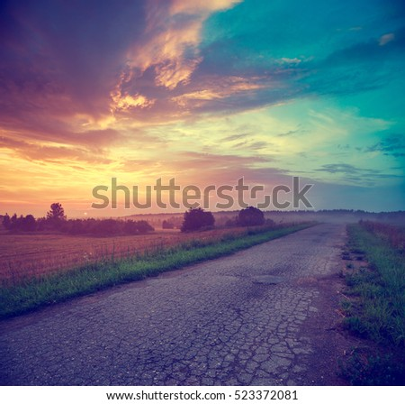 Summer Landscape with Field and Country Road Leading in the Fog. Dramatic Sky at Sunset Background. Beautiful Nature Background. Toned Photo with Copy Space.