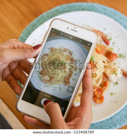 Woman taking photo of spaghetti with smartphone