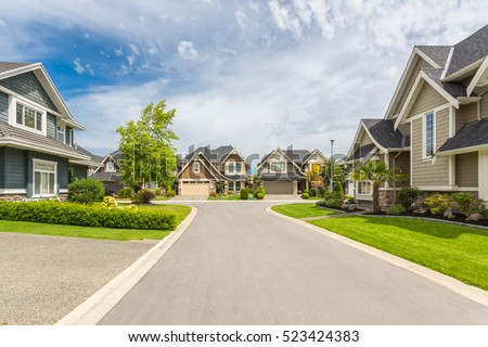 Nicely trimmed and manicured garden in front of a luxury house on a sunny summer day. Street of houses in the suburbs of Canada. Royalty-Free Stock Photo #523424383