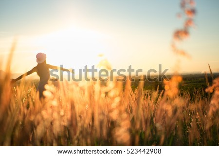 Trendy girl in stylish summer dress with beautiful hat walking in the field with flowers in sunlight Royalty-Free Stock Photo #523442908