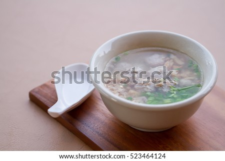 Rice boiled with pork, garlic and coriander bowl on wood board with spoon. #523464124