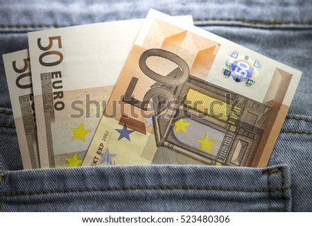 Several fifty euro banknotes stuck out blue jeans pocket. Close up image. Hologram shining. #523480306