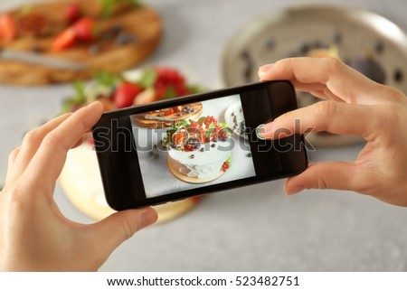 Blogger making photo of delicious creamy cake, closeup