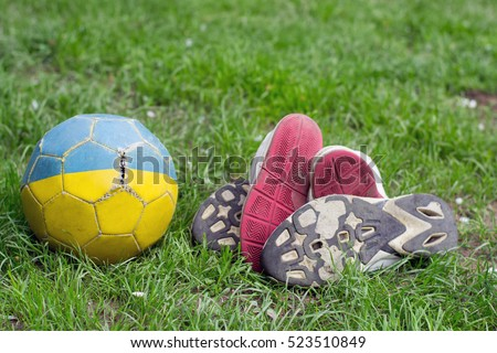 children and adults old shoes with worn soles and old shabby myach football on grass #523510849