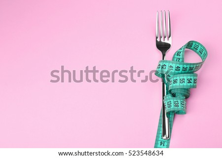 Measuring tape wrapped around fork lying on color surface. Diet concept Royalty-Free Stock Photo #523548634