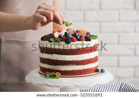 Woman decorating delicious cake #523551691