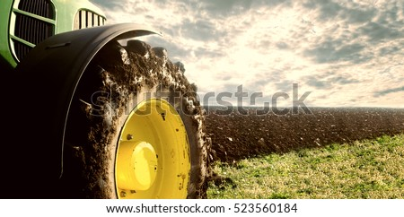 Agriculture. Tractor plowing field. Wheels covered in mud, field in the backround. Cultivated field. Agronomy, farming, husbandry concept. Royalty-Free Stock Photo #523560184