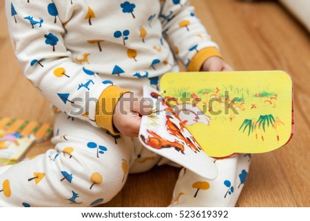 baby open picture book with curiosity as sit on floor